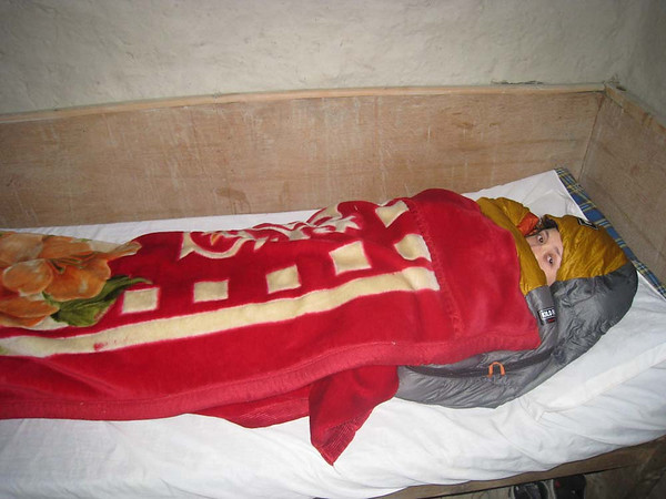 Claudine in her mummy sleeping bag and under a traditional Tibetan blanket (temperatures dipped to the low 40s in our room at night)